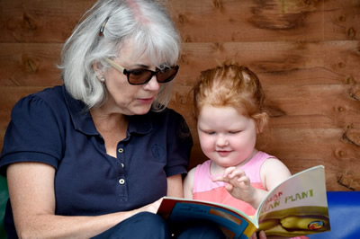 Tilly enjoying a story book at pre-school with Elaine Hough, Early Years Practitioner