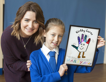 Kirkby C of E pupil Milly Perry, 10, pictured with Cllr Steff O'Keeffe and her winning design in the Knowsley Super Hero Foster Carers competition